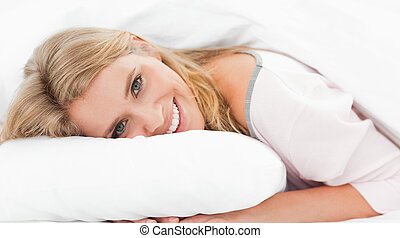 A woman lying in bed with her hands under a pillow and head on it, with her eyes open and smiling.