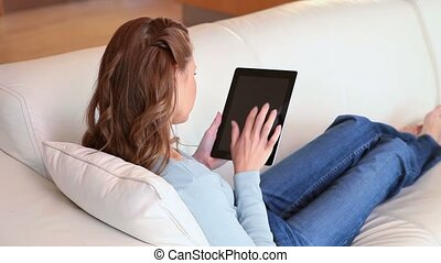 A woman lying on the couch with a tablet in her hands