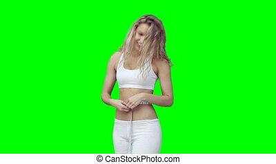 A woman measuring her waist line