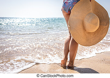 A woman near the sea holds a large hat in her hands.