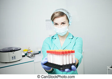 A woman nurse doctor in a medical mask holds test tubes for a blood test
