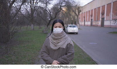 A woman of Asian ethnicity in a protective mask is standing on the street near an old abandoned factory, close-up with the camera leaving for the general plan. Prores 422