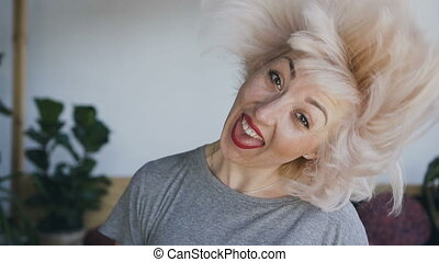 A woman of natural beauty with white hair and red lipstick laughs and waved her head to the left and to the right, her hair beautifully flies in different directions.