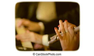 a woman on a flute accompanies a piano. retro style film...