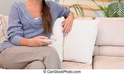 A woman on the couch changing the channel of the television...