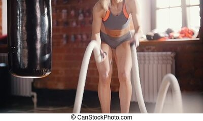 A woman on training in the gym. Training her hands with ropes hitting
