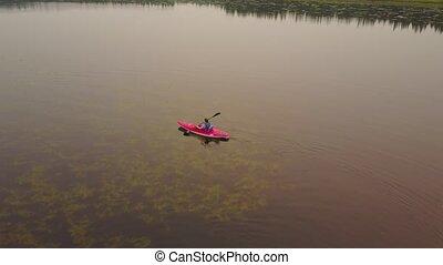 A woman paddling in kayak enjoying a calm, misty lake. - ...