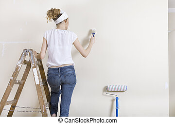 A woman painting wall on ladder