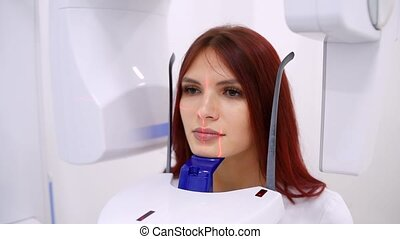 A girl patient makes a panoramic X-ray of the oral cavity using an orthopantomographic apparatus. close-up