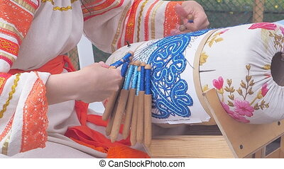 a woman performs a lace weave on the spokes.