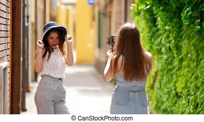 A woman photographs her friend who poses for a photo - Mid...