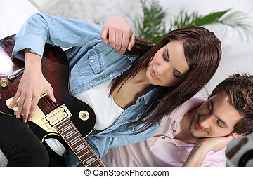 a woman playing guitar and her boyfriend