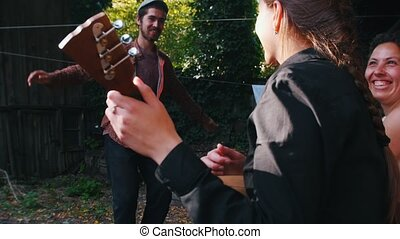 A woman playing the balalaika and a man dancing folklore dancing near the country house - bright sunlight. Mid shot
