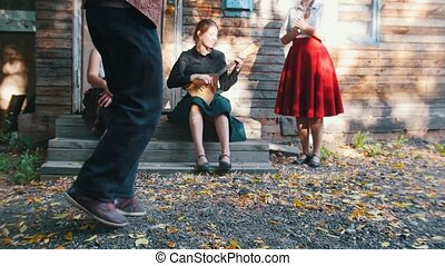 A woman playing the balalaika and a man dancing folklore dancing near the country house. Mid shot