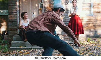 A woman playing the balalaika and a man dancing russian folklore dancing near the country house - bright sunlight. Mid shot