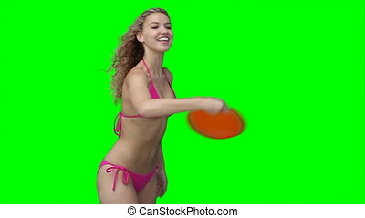 A woman plays with a Frisbee while smiling