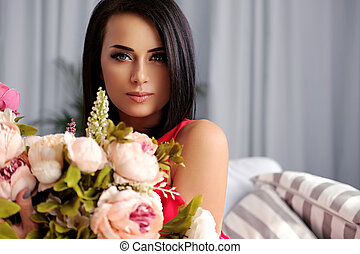 A woman posing with the colorful flower bouquet.