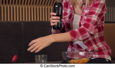 A woman pouring cola into a glass