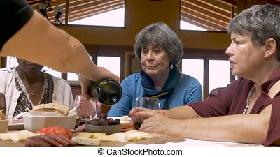 A woman pouring wine for her diverse group of friends at a party