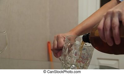 A woman pours beer into a glass mug.