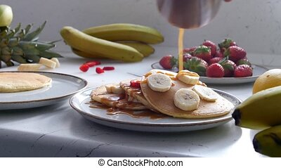 A woman pours condensed milk on pancakes with bananas
