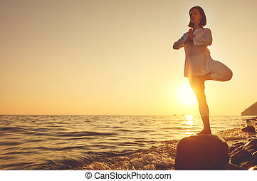 woman practices yoga and meditates   on sunset beach