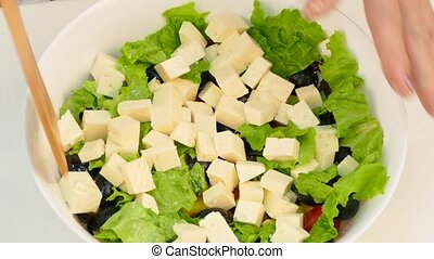 A woman prepares a Greek salad of vegetables and cheese with olive oil.