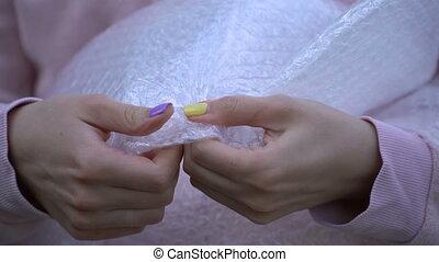 A woman presses a bubble wrap. - A woman presses a bubble...