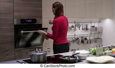 A woman pulls out a dish from the oven