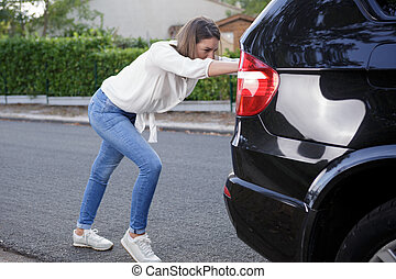 a woman pushes the car