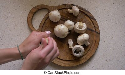A woman puts champignons on a wooden board to cut them. ...