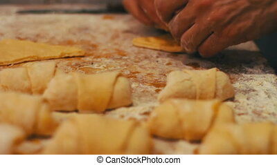 A woman puts on fresh pieces of dough apricot jam