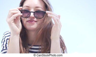 A woman puts on her face sunglasses