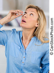 a woman putting eye drops in her eyes