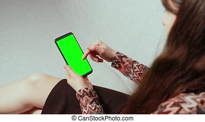 A woman read ads on the Internet on the phone, showing thumb up gesture. Video Chromakey Green Screen. News or Advertisingon. Scrolls up, presses on the screen, zooms in and shows the screen close