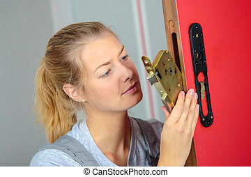 a woman replacing the lock