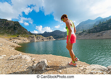 A woman rests between fitness training in the mountains