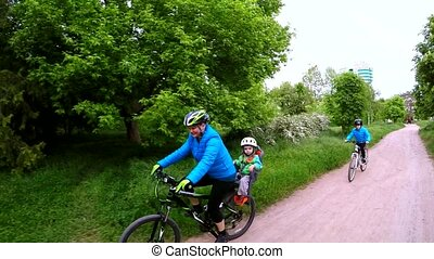A woman rides a bicycle and carries in the trunk of a child. Slow motion.