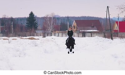 A woman riding a horse in a village. Mid shot