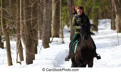 A woman riding a horse in the forest. Mid shot