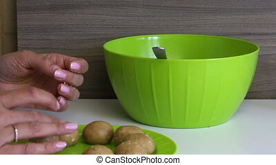 A woman rolls balls of biscuits with condensed milk in her hands. Ready balls puts on a plate. Cooking basics for cake pops.