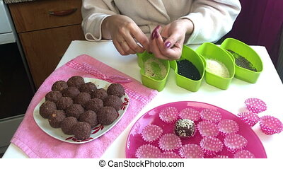 A woman rolls balls of cocoa powder and melted butter in...