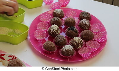 A woman rolls sesame balls of a mixture of cocoa powder and...