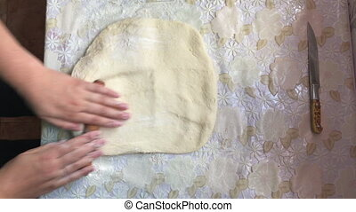 A woman rolls the dough with a wooden rolling pin. Preparation of buns with cinnamon at home