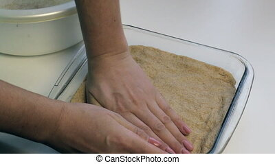 A woman rubs her hands with a dough cake laid in a baking...