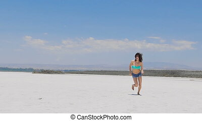 A woman running at a very white salt lake in Cyprus - A...
