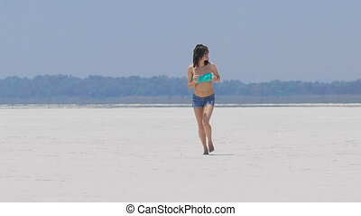 A woman running at a very white salt lake in Cyprus