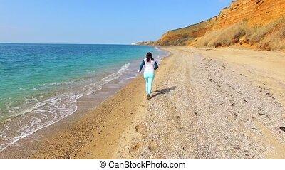 A woman runs along the coastline and the camera follows her.