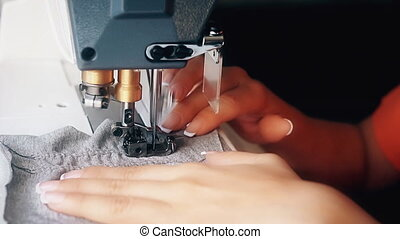 A woman sews on an industrial flat-seam sewing machine. ...