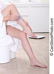 a woman shaving her legs